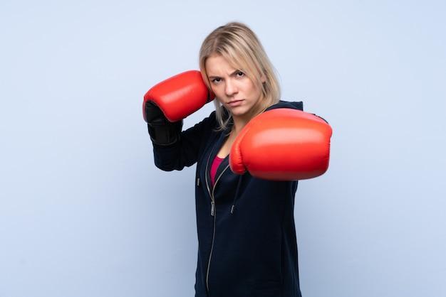 Mulher loira esporte jovem sobre parede azul isolada com luvas de boxe