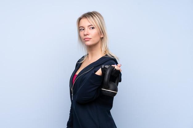Mulher loira esporte jovem sobre parede azul isolada, fazendo levantamento de peso com kettlebell