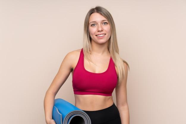 Mulher loira esporte jovem sobre parede isolada com uma esteira e sorrindo
