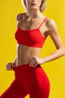 Mulher loira esportiva com corpo perfeito em roupas esportivas vermelhas ajustando leggings em pé contra amarelo