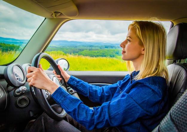 Mulher loira está dirigindo um carro com montanhas atrás