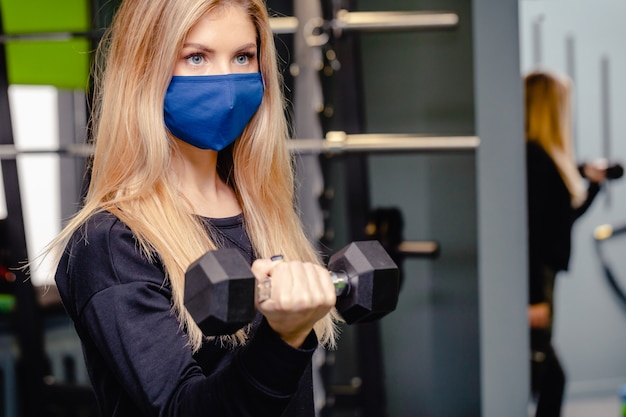 Mulher loira está treinando na academia durante a pandemia. menina faz exercícios com máscaras médicas. ginásio durante o período do coronavírus. coronavírus, doença, conceito de infecção.