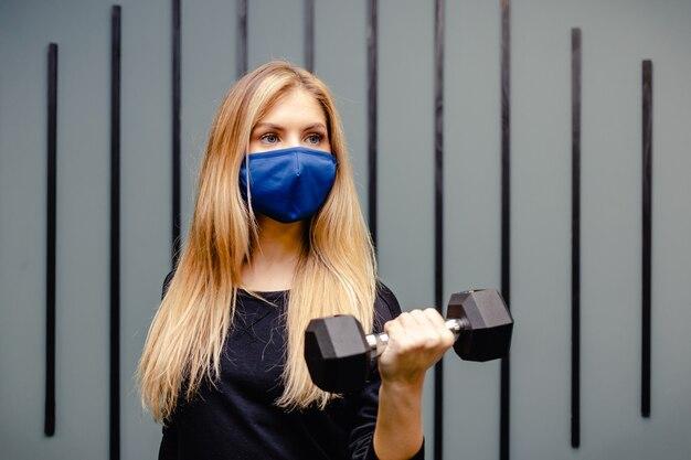 Mulher loira está treinando na academia durante a pandemia. menina fazendo exercícios com máscara médica