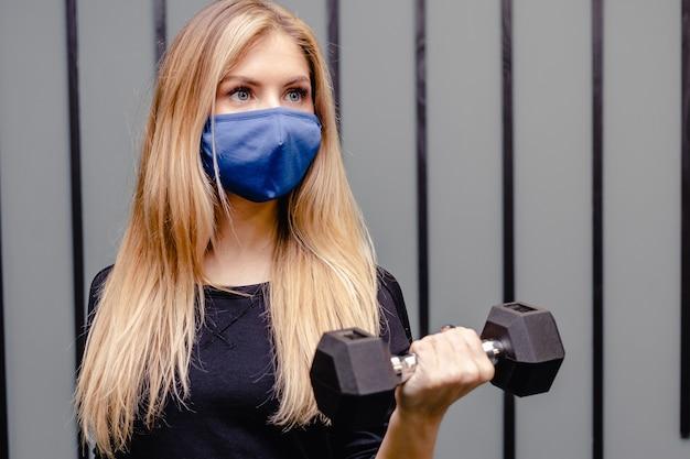 Mulher loira está treinando na academia durante a pandemia.