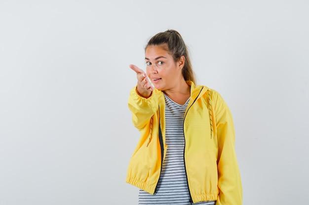 Mulher loira esticando a mão para a frente como um convite para entrar em uma jaqueta bomber amarela e camisa listrada e bonita