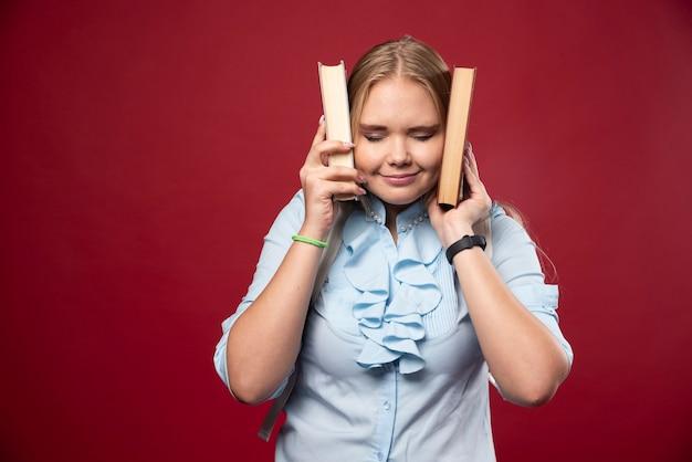 Mulher loira estudante segura seus livros e cobre os ouvidos com eles.