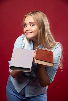 Mulher loira estudante segura seus livros e parece agradável.