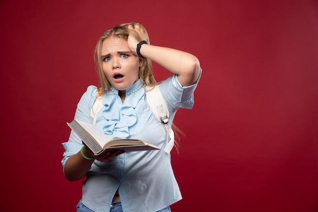 Mulher loira estudante segura seus livros e parece apavorada.