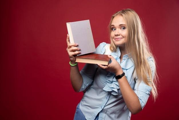 Mulher loira estudante segura seus livros e se sente feliz.
