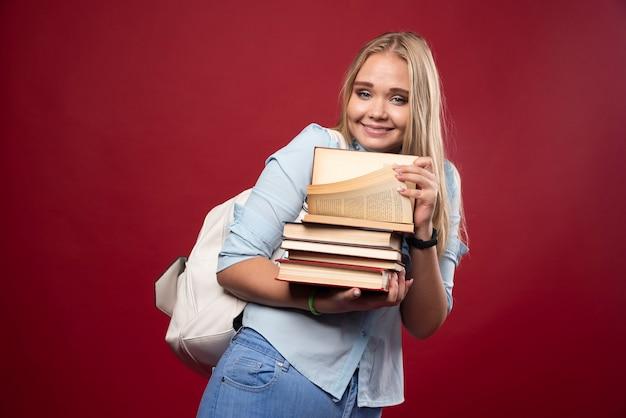 Mulher loira estudante segurando uma pilha de livros e parece positiva.