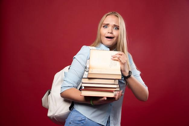 Mulher loira estudante segurando uma pilha pesada de livros e parece cansada.