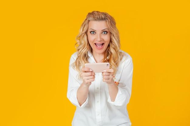 Mulher loira europeia excitada em camisa branca, parece surpresa e animada, joga novo jogo incrível para smartphone, grita e sorri feliz, ganha. de pé sobre um fundo amarelo.