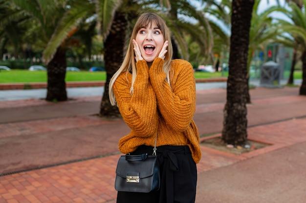 Mulher loira excitada com óculos escuros elegantes posando à beira-mar em barcelona