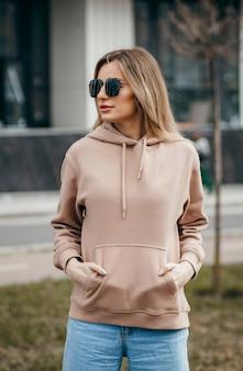 Mulher loira fashion com óculos de capuz marrom grande e maquete de jeans para logotipo ou design de marca