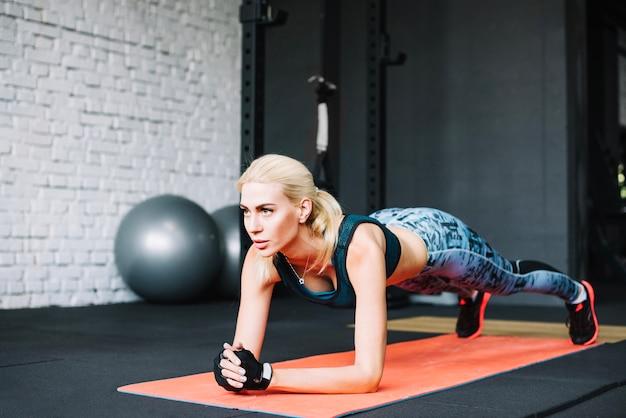 Mulher loira fazendo exercício de prancha