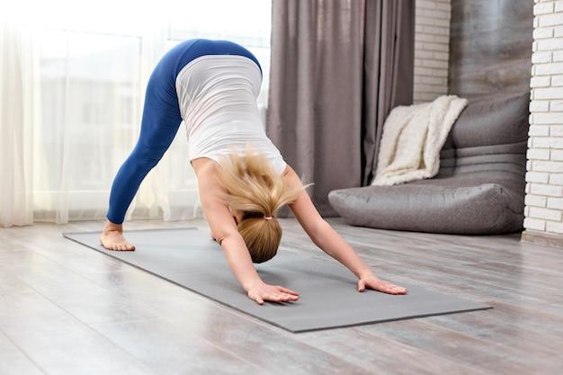 Mulher loira fazendo exercícios adho mukha svanasana sozinha em casa
