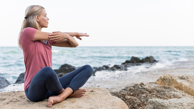 Mulher loira fazendo ioga na praia