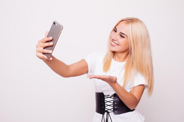 Mulher loira fazendo selfie isolado