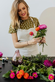 Mulher loira fazendo um buquê de flores