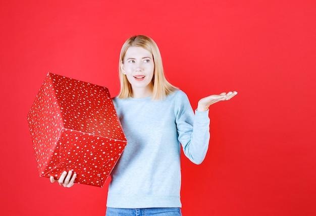 Mulher loira fazendo um sinal com a mão enquanto segura a caixa de presente vermelha com a mão direita