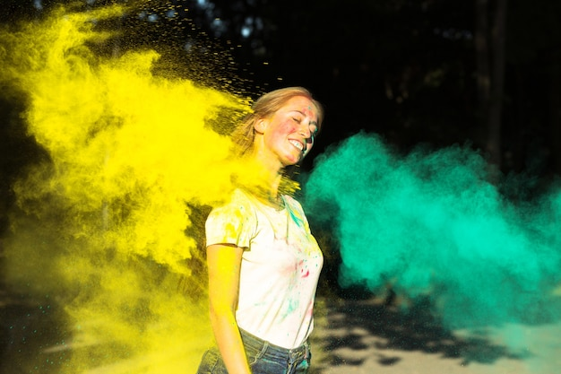 Mulher loira feliz brincando com tinta seca amarela e verde holi no parque