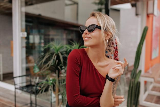 Mulher loira feliz com óculos escuros e vestido vermelho