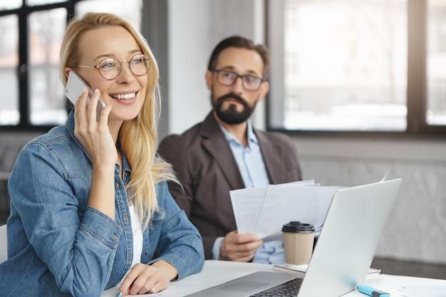 Mulher loira feliz conversando com um colega