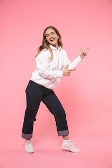 Mulher loira feliz de comprimento total usando roupas casuais apontando para longe e olhando para a frente sobre a parede rosa