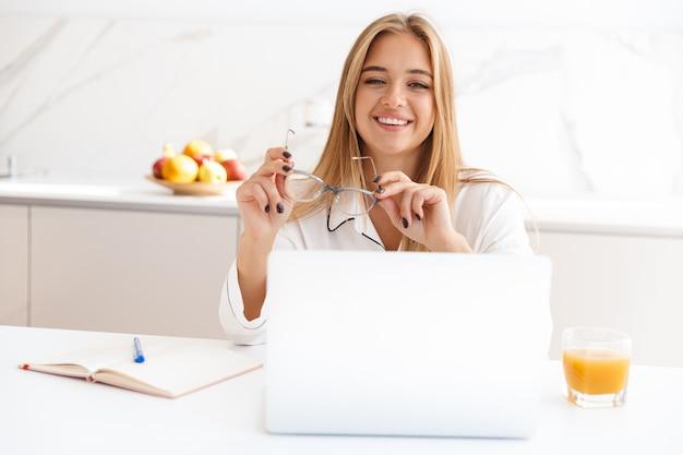 Mulher loira feliz de pijama trabalhando com laptop e diário enquanto está sentado à mesa na cozinha bem iluminada