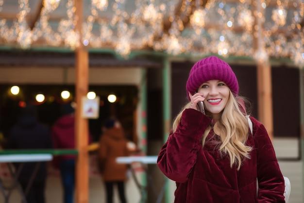 Mulher loira feliz falando no celular ao fundo das luzes de natal