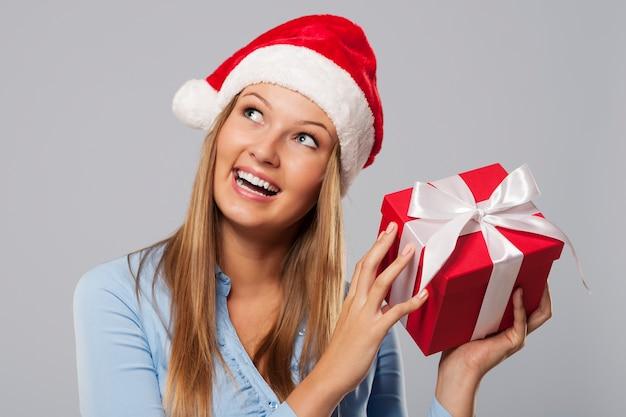 Mulher loira feliz segurando um pequeno presente vermelho