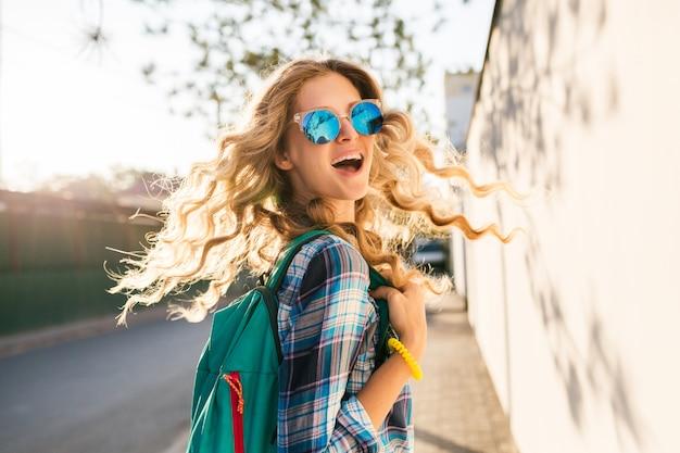 Mulher loira feliz sorridente e elegante andando na rua com uma mochila