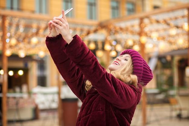 Mulher loira feliz vestida com roupas quentes fazendo selfie no fundo de uma guirlanda em kiev