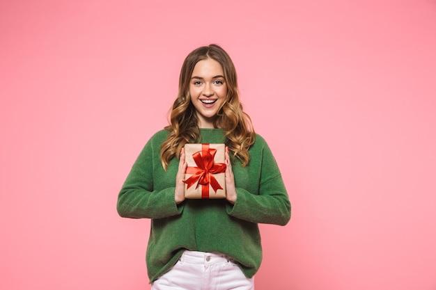Mulher loira feliz vestindo um suéter verde segurando uma caixa de presente e olhando para a frente sobre a parede rosa