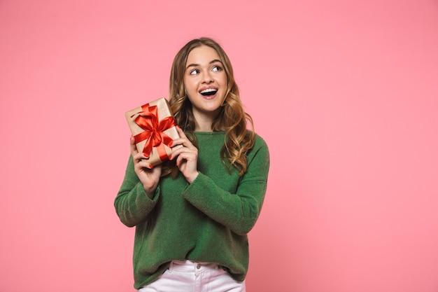 Mulher loira feliz vestindo um suéter verde segurando uma caixa de presente e olhando por cima da parede rosa