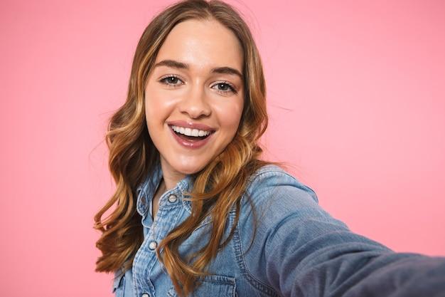Mulher loira feliz vestindo uma camisa jeans fazendo selfie e olhando para a frente sobre a parede rosa