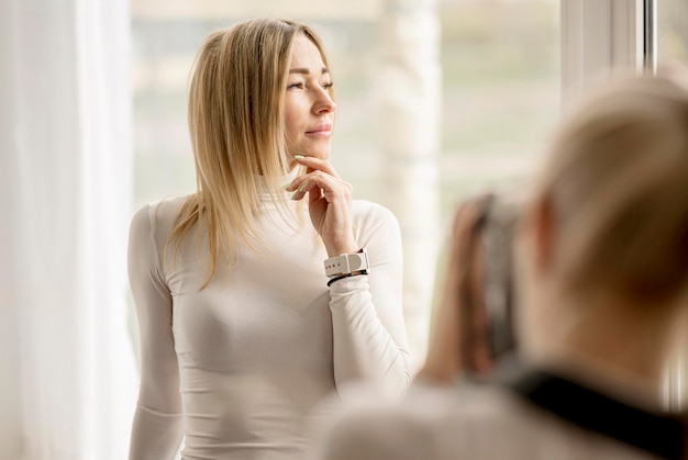 Mulher loira feminina e fotógrafo turva