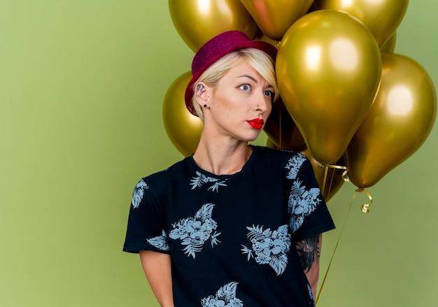 Mulher loira festeira de cenho franzido com chapéu de festa em pé na frente de balões, olhando para o lado, mantendo as mãos atrás das costas isoladas na parede verde oliva com espaço de cópia