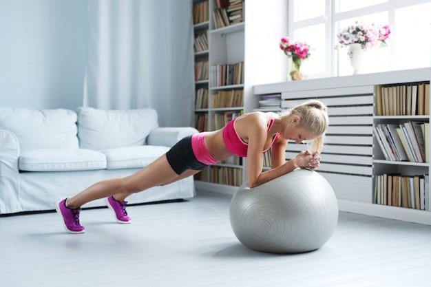 Mulher loira fitness fazendo alongamentos com sua bola de exercício em casa
