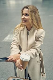 Mulher loira fofa expressando positividade enquanto aprecia seu café antes da viagem para a conferência