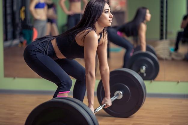 Mulher loira forte exercitar com barra no ginásio. linda garota se preparando para o treino de halterofilismo. esportes, conceito de fitness.