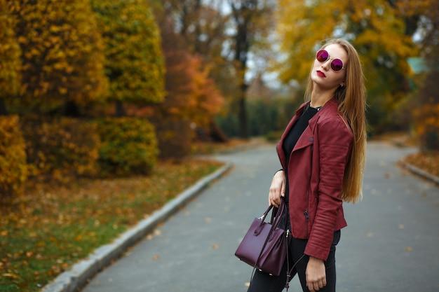 Mulher loira glamour com lábios vermelhos, vestindo jaqueta de couro, bolsa e óculos vermelhos. espaço para texto