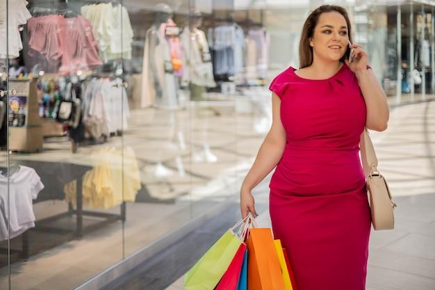 Mulher loira glamourosa plus size em um vestido rosa sedutor indo com sacola de compras falando smartphone