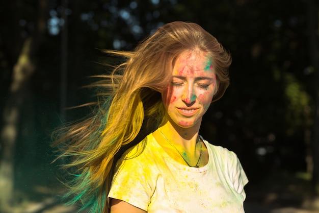 Mulher loira gloriosa com cabelo esvoaçante celebrando o festival holi