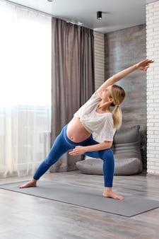 Mulher loira grávida bonita e desportiva fazendo exercício de estocada em pé em posição de ângulo lateral estendido em casa