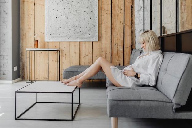 Mulher loira grávida relaxando em um sofá cinza