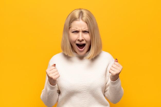 Mulher loira gritando agressivamente com olhar irritado, frustrado e irritado e punhos cerrados, sentindo-se furiosa