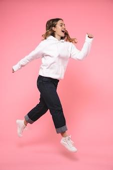 Mulher loira gritando, de corpo inteiro, usando roupas casuais, correndo pela parede rosa
