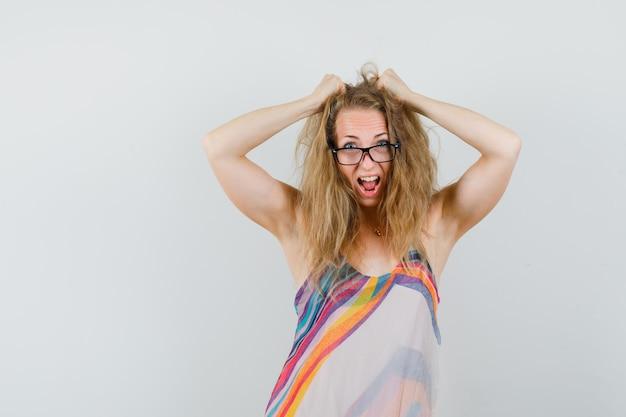Mulher loira gritando enquanto toca no cabelo com um vestido de verão e parecendo louca.