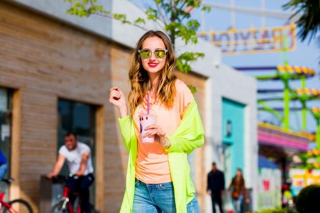 Mulher loira hippie de óculos escuros e posando para coquetel ao ar livre
